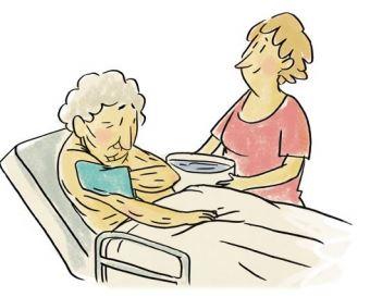 Ältere Frau wäscht sich mit Waschlappen im Bett den Arm, eine junge Frau hält eine Schüssel mit Wasser.